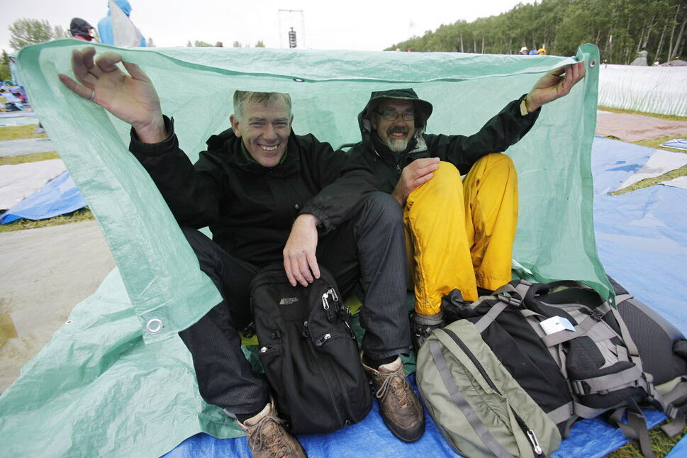 Brothers Keith (left) and Lesly Derksen take shelter under a tarp as they enjoy festivities on the final day of Folk Fest Sunday, July 13, 2014.  (John Woods / Winnipeg Free Press)