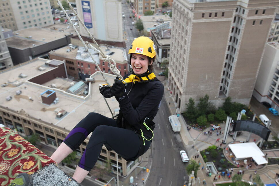 Megan Hemenway is all smiles as she steps off the ledge of the RBC building just before she rappels down 200 feet during the annual Easter Seals Drop Zone event.   (Ruth Bonneville / Winnipeg Free Press)