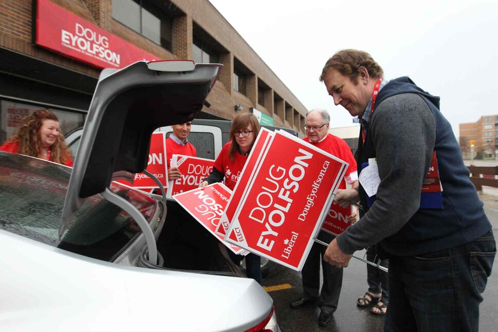 Doug Eyolfson, Liberal candidate in St. James, Charleswood load up signs into a vehicle outside his office Wednesday.