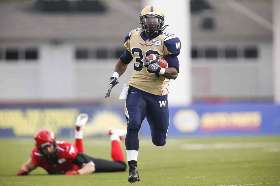 Winnipeg Blue Bombers' Will Ford returns a kick as Calgary Stampeders' Eric Fraser watches him get away during the first half. (Jeff McIntosh / The Canadian Press)