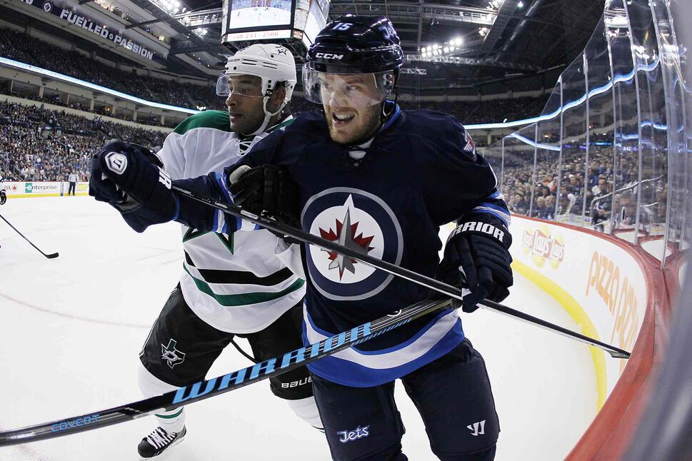 Dallas Stars' Trevor Daley (6) and Winnipeg Jets' Matt Halishchuk (15) fight for position in the Stars' corner during the second period. (JOHN WOODS / THE CANADIAN PRESS)