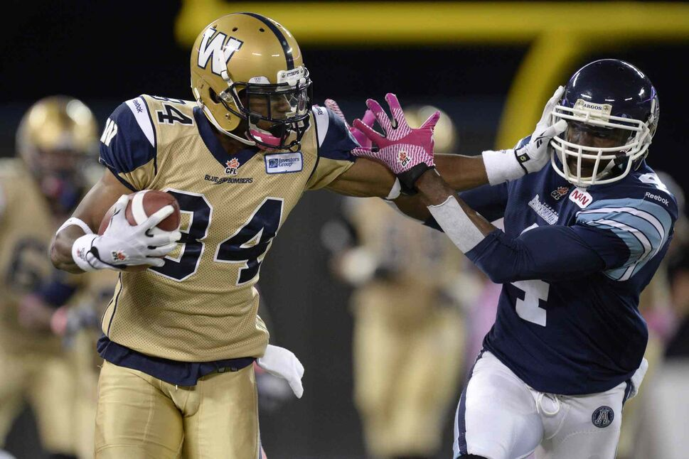 Winnipeg Blue Bombers' Wallace Miles holds off Pacino Horne of the Toronto Argonauts after making a catch during the first quarter. (Frank Gunn / The Canadian Press)