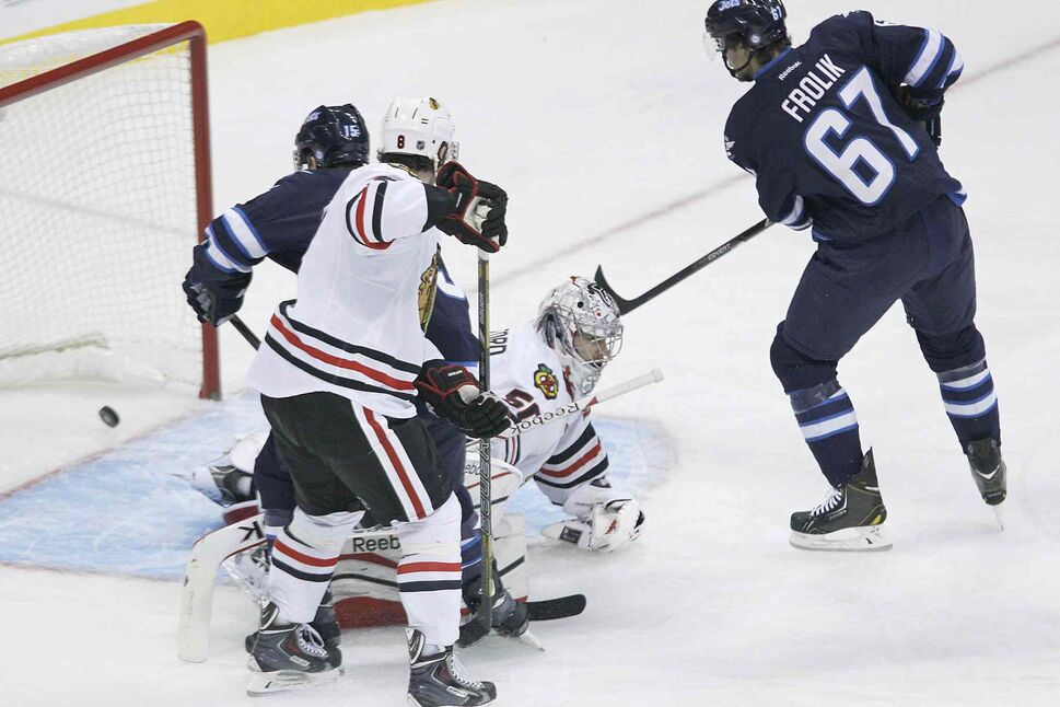 Chicago Blackhawks' goaltender Corey Crawford (bottom) can't stop a shot from the point by Winnipeg Jets defenceman Toby Enstrom as Matt Halishchuk (15) and Michael Frolik (67) of the Jets and Hawks' Nick Leddy (8) look for the rebound during the first period. (John Woods / The Canadian Press)