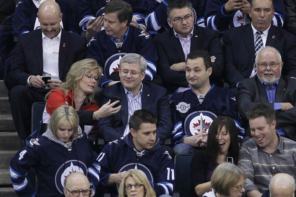 Conservative MP Shelly Glover (left) shows Prime Minister Stephen Harper something on her phone as Conservative MP Rod Bruinooge (right) looks on. (JOHN WOODS / THE CANADIAN PRESS)