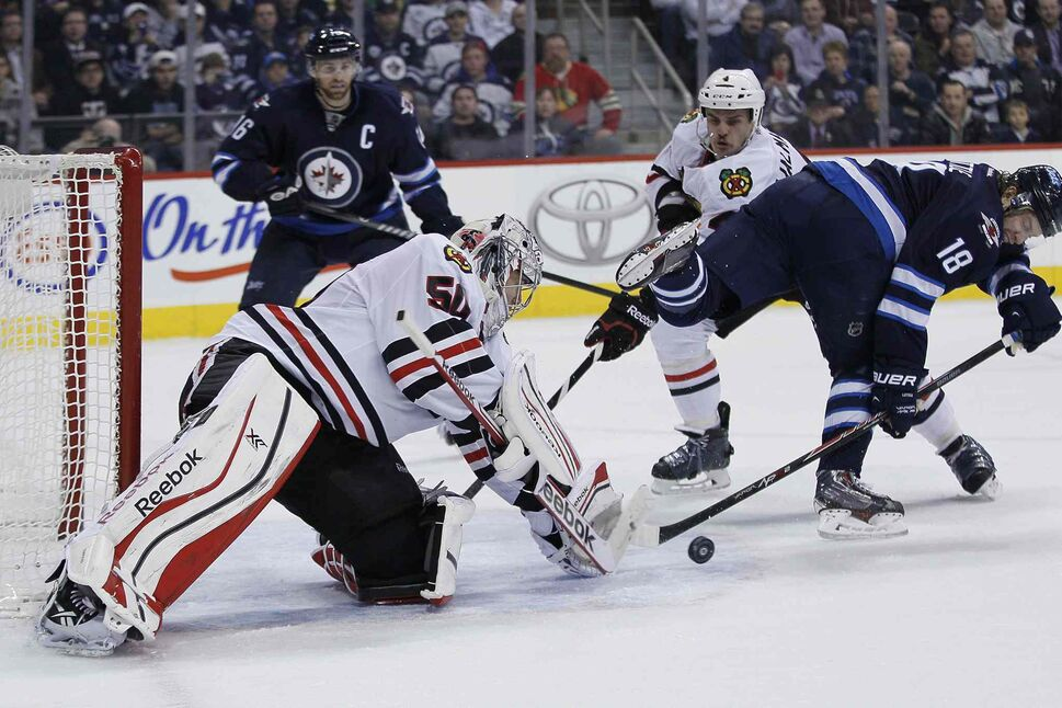 Chicago Blackhawks goaltender Corey Crawford (50) stops a backhander by Winnipeg Jets centre Bryan Little (18) as Hawks' Niklas Hjalmarsson (centre right) and Andrew Ladd (left) look for the rebound during the second period. (JOHN WOODS / THE CANADIAN PRESS)