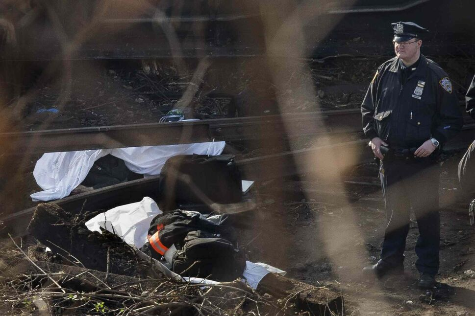 A police officer stands guard over a body at the scene of the passenger train derailment. (John Minchillo / The Associated Press)