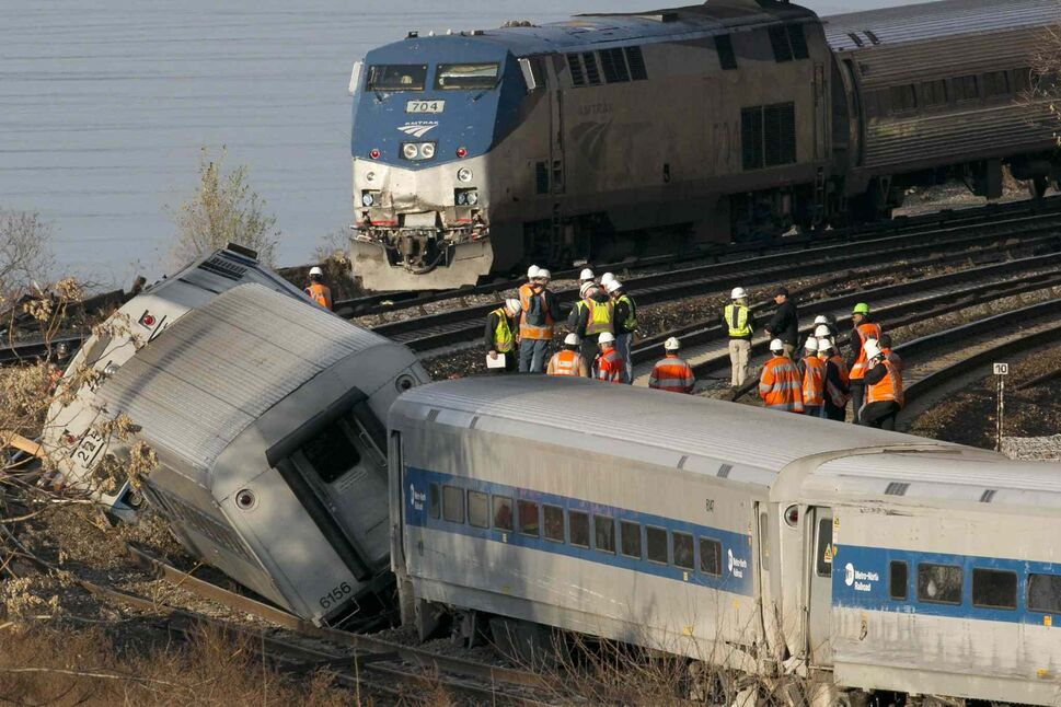 An Amtrak train (top) traveling on an unaffected track passes a derailed Metro North commuter train Sunday. (Mark Lennihan / The Associated Press)