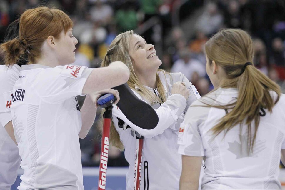 Skip Jennifer Jones (centre right) and her team (from left) Jill Officer, Dawn McEwen and Kaitlyn Lawes watch the replay of her three-point shot in the second end. (John Woods / The Canadian Press)