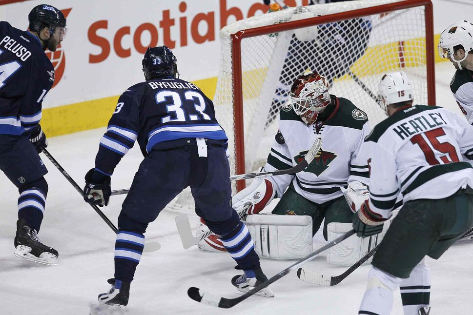 Winnipeg Jets defenceman Dustin Byfuglien (33) scores on Minnesota Wild goaltender Niklas Backstrom (32) as Anthony Peluso (left) of the Jets and Dany Heatley and Nate Prosser of the Wild look on during the first period. (JOHN WOODS / THE CANADIAN PRESS)