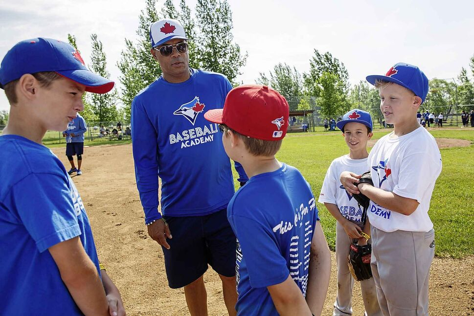 Former Blue Jays second baseman Roberto Alomar gives kids pointers on catching and throwing the ball.