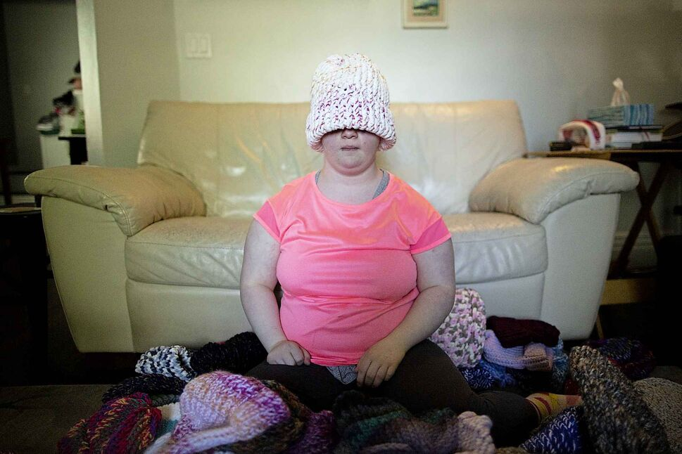 Solveig Meinhardt tries on one of her knitted hats. (Andrew Ryan / Winnipeg Free Press)