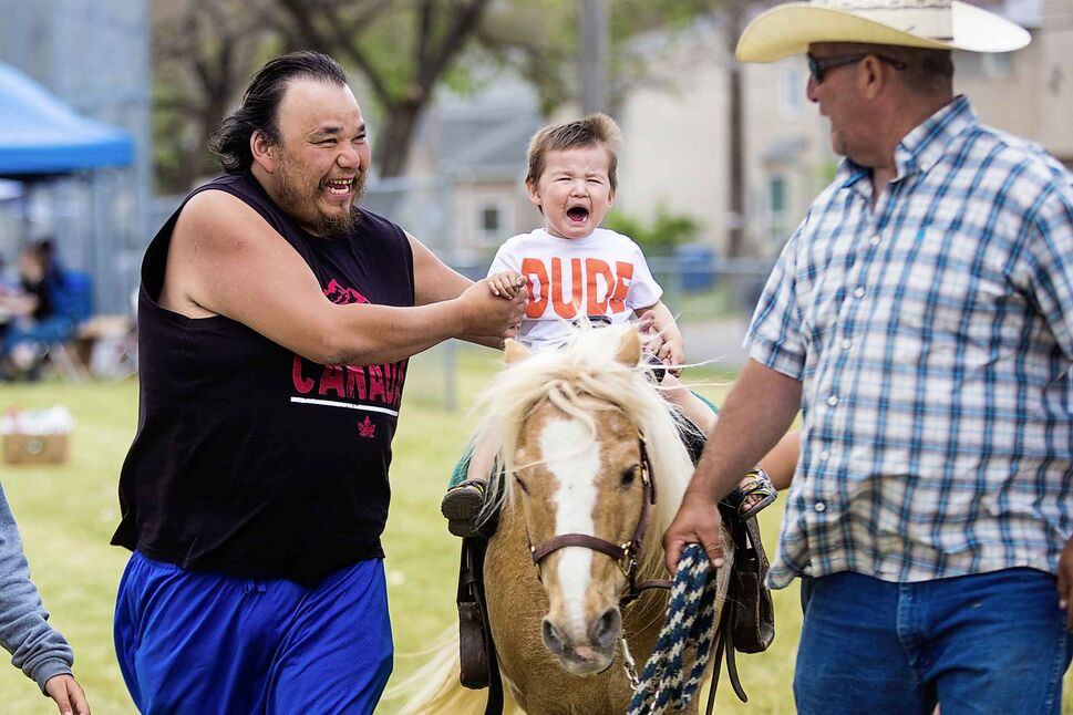 MIKAELA MACKENZIE / WINNIPEG FREE PRESS Two-year-old Jace Keeper decides that he doesn't like the pony ride as his uncle, Rocky Hudson, holds him up and Barry Sanderson leads the animal at Aboriginal Day festivities at the Freighthouse Community Centre on June 21.