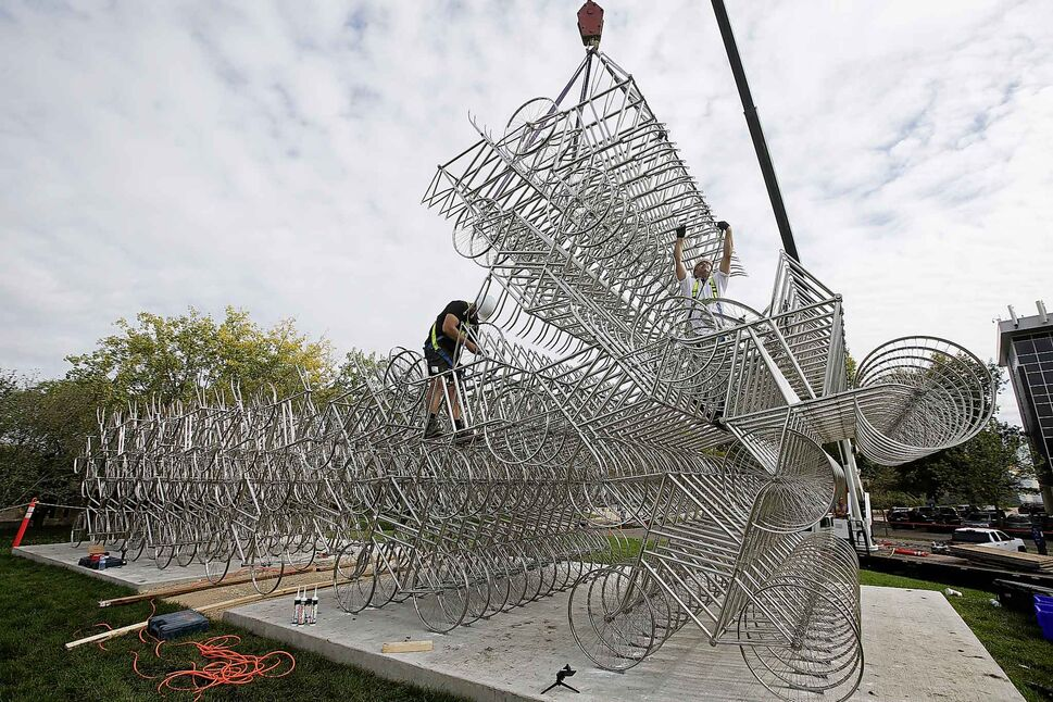 Matt Syles (left) and Dan Page, art installation technicians with MTEC, work on installing a bicycle sculpture by artist Ai Weiwei in Winnipeg Tuesday. (JOHN WOODS / WINNIPEG FREE PRESS)