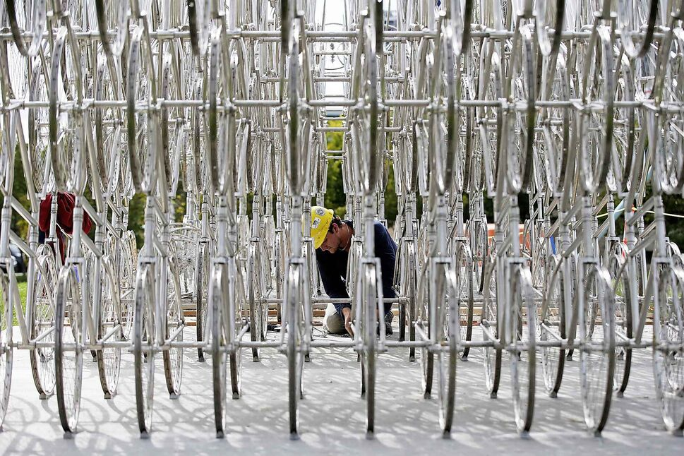 Kyle Peters, art installation technicians with Westland, works on installing a bicycle sculpture by artist Ai Weiwei in Winnipeg Tuesday. (JOHN WOODS / WINNIPEG FREE PRESS)