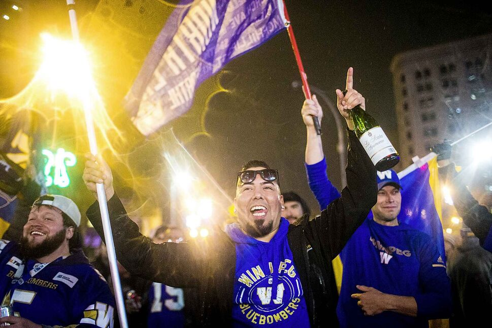 Bombers fans celebrate the Grey Cup win at Portage and Main in Winnipeg on Sunday. (Mikaela MacKenzie / Winnipeg Free Press)