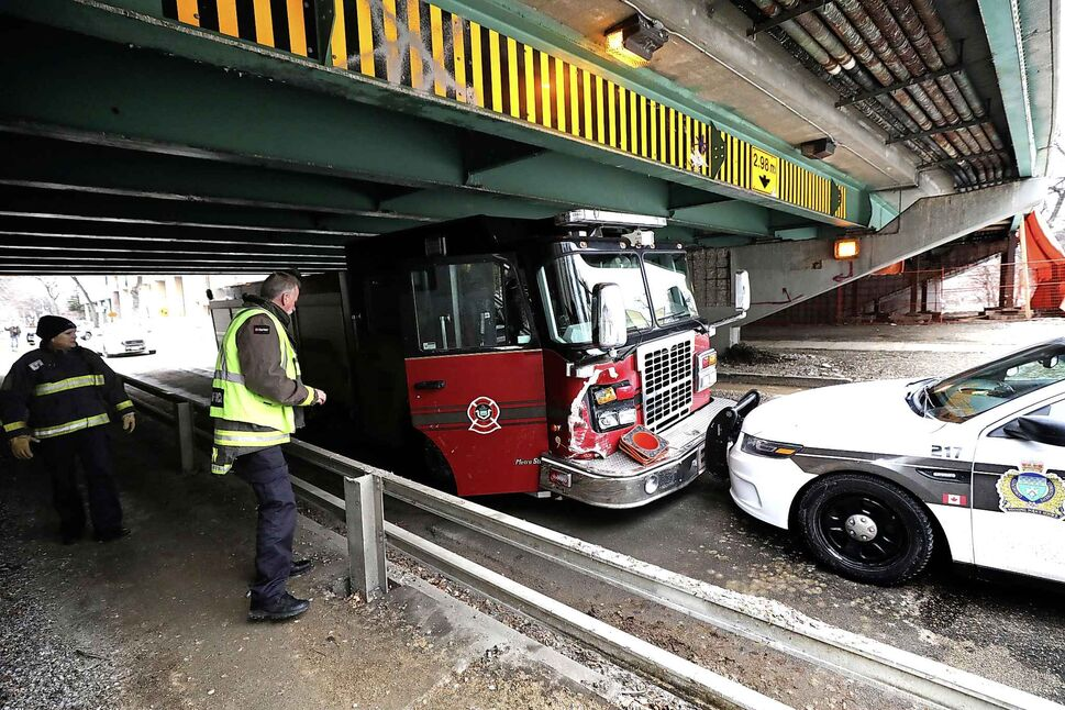 RUTH BONNEVILLE  /  WINNIPEG FREE PRESS  Winnipeg Police Officers and fire crews view the damage on a stolen fire truck that was stopped under the Donald Street Bridge on Nov. 29.