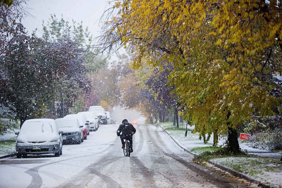 MIKAELA MACKENZIE / WINNIPEG FREE PRESS A cyclist makes their way through the slushy streets in Wolseley during the first snowfall of the year in Winnipeg on Oct. 10.