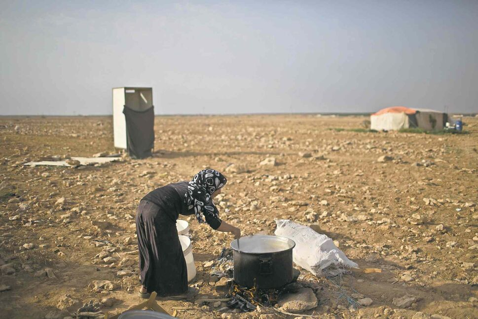 A Syrian refugee cooks on a fire outside her tent at an informal settlement near the Syrian border. (CP)