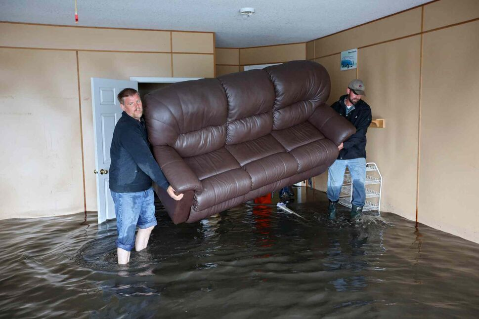 Mr. Froese and Ivan Penner carry a couch from the flooded home of Greg and Amy Baerg to a waiting trailer in Cromer. (Tim Smith / Brandon Sun)