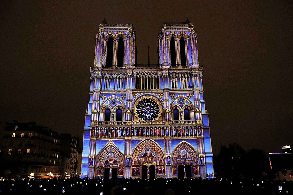 """The Notre Dame cathedral is illuminated during a light show called """"Dame de Cœur"""" to celebrate the centenary of the First World War, in Paris, Wednesday, Nov. 8, 2017. (Christophe Ena / The Associated Press files)"""