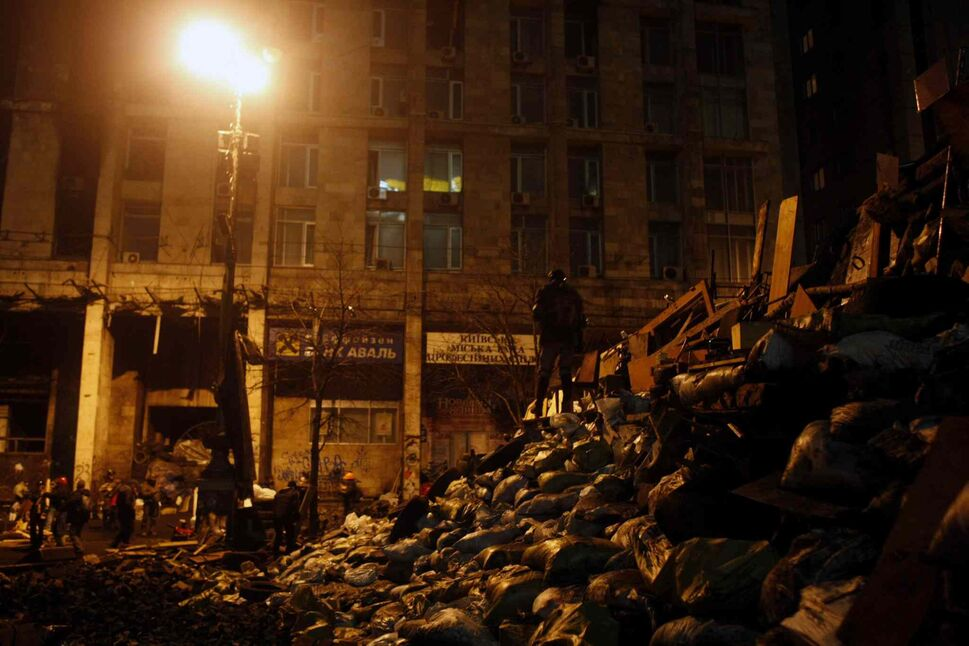 An anti-government protester stands atop a barricade at Independence Square in Kyiv on Thursday. Protesters advanced on police lines in the heart of the Ukrainian capital Thursday, prompting government snipers to shoot back and kill scores of people in the country's deadliest day since the breakup of the Soviet Union a quarter-century ago. (Marko Drobnjakovic / The Associated Press)