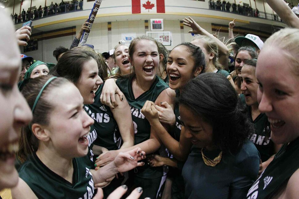 Members of the Vincent Massey Trojans celebrate a 70-53 win over the Sisler Spartans in the high school AAAA provincial basketball championship game at the University of Manitoba's Investors Group Athletic Centre Monday, March 24, 2014.  (JOHN WOODS / WINNIPEG FREE PRESS)