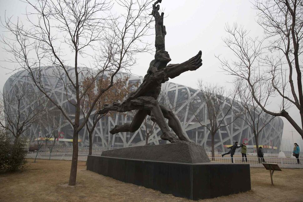 A tourist poses near giant sculptures near the iconic Bird's Nest National Stadium in Beijing, China.  Beijing, which spent more than $2 billion to build 31 venues for the 2008 Summer Games, is reaping some income and tourism benefits from two flagship venues, though many sites need government subsidies to meet hefty operation and maintenance costs.  (Ng Han Guan / The Associated Press)