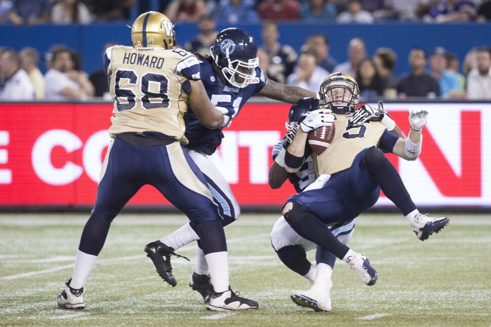 Winnipeg Blue Bombers quarter back Drew Willy (right) is sacked by Toronto Argonauts Tristan Okpalaugo (obscured) during the first half. (Chris Young / The Canadian Press)