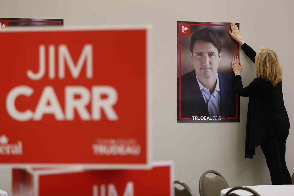 Judy Kovalik, a volunteer for the Jim Carr Liberal campaign in Winnipeg South Centre, hangs signs prior to the election night party Monday, Oct. 19, 2015.  (John Woods / The Canadian Press)