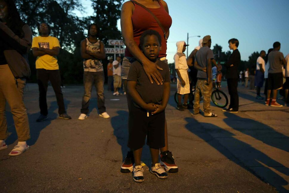 Jeremiah Parker, 4, stands in front of his mother, Shatara, as they attend a protest Wednesday. Nights of unrest have vied with calls for calm in a St. Louis suburb where Michael Brown, an unarmed black teenager was killed by police.  (Jeff Roberson / The Associated Press)