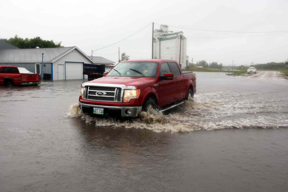 A truck makes its way through flood waters covering Highway 256 in the village of Cromer. (Tim Smith / Brandon Sun)