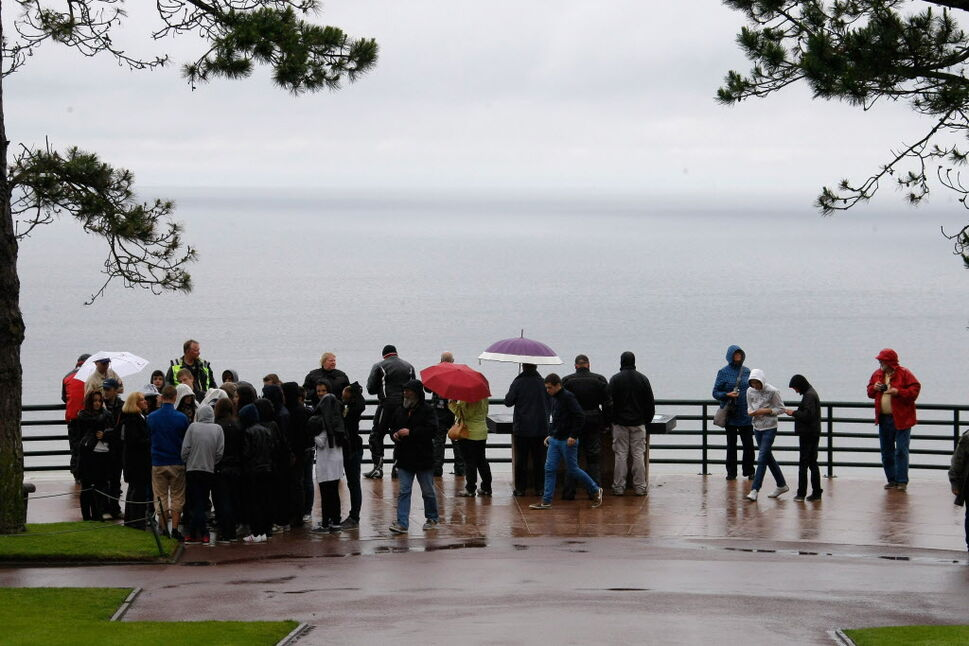 Visitors look at the Omaha Beach from the Normandy American Cemetery and Memorial, in Colleville sur Mer, France, Wednesday June 4.   (Claude Paris / The Associated Press)