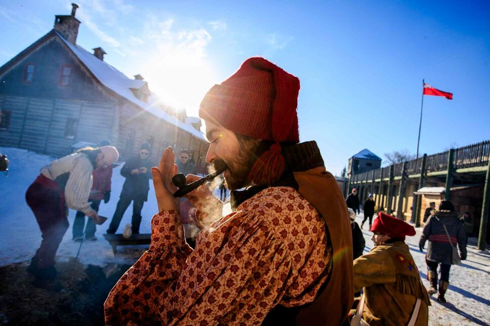 Barney Morin lights his tobacco pipe before telling a story at a camp du feu (fire camp) at Festival du Voyageur on Louis Riel Day. Melissa Tait / Winnipeg Free Press