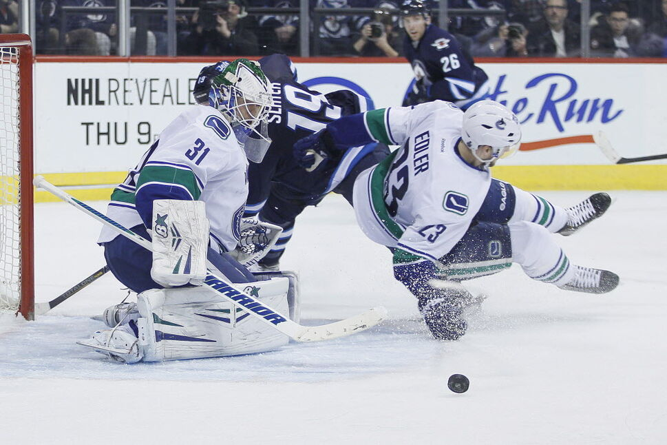 Winnipeg Jets' Jim Slater (19) and Vancouver Canucks' Alexander Edler (23) collide as goaltender Eddie Lack (31) saves the shot from Slater during second period NHL action. (JOHN WOODS / THE CANADIAN PRESS)