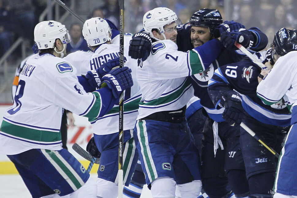 Vancouver Canucks' Shawn Matthias (27) holds back Winnipeg Jets' Dustin Byfuglien (33) from Canucks' Christopher Tanev (8) during second period NHL action. (JOHN WOODS / THE CANADIAN PRESS)