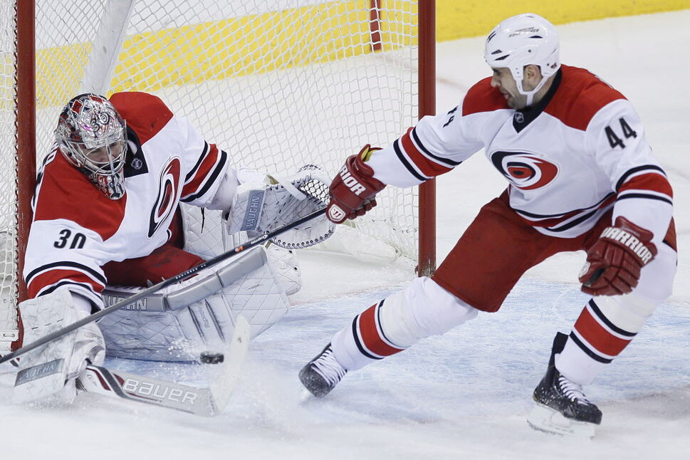 Carolina Hurricanes goaltender Cam Ward (30) stops the shot from Winnipeg Jets' Evander Kane (9) as Jay Harrison (44) looks on during first period NHL action in Winnipeg on Saturday, March 22, 2014.  (JOHN WOODS / THE CANADIAN PRESS)