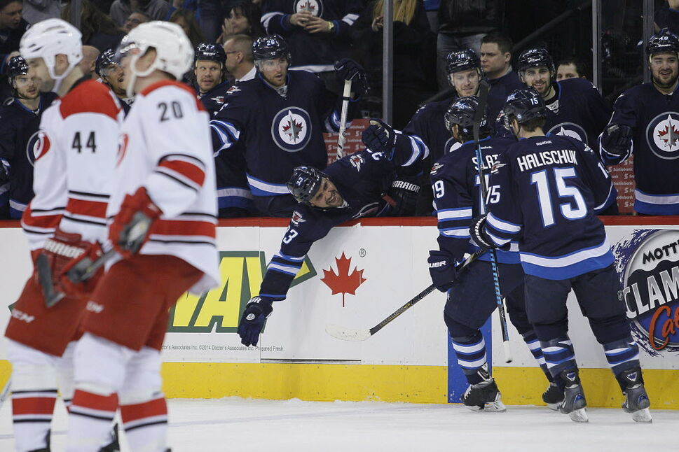 Winnipeg Jets' Dustin Byfuglien (33) celebrates after Jim Slater (19) tips a shot past Carolina Hurricanes' goaltender Cam Ward (30) during second period NHL action. (JOHN WOODS / THE CANADIAN PRESS)
