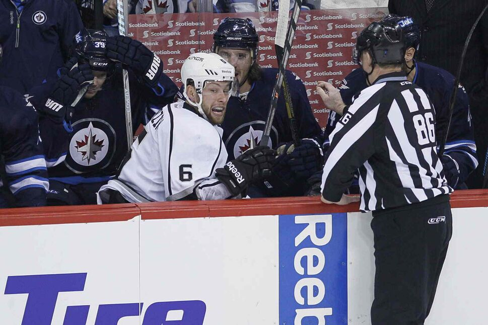 Los Angeles Kings' Jake Muzzin (6) climbs out of the Winnipeg Jets' bench after being dumped over the boards.  (John Woods / The Canadian Press)