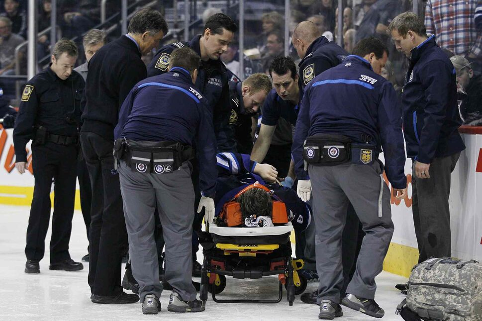 Winnipeg Jets' Jacob Trouba (8) is attended to by paramedics after crashing head first into the boards during second period NHL action against the St. Louis Blues in Winnipeg on Friday, October 18, 2013. THE CANADIAN PRESS/John Woods (JOHN WOODS / THE CANADIAN PRESS)