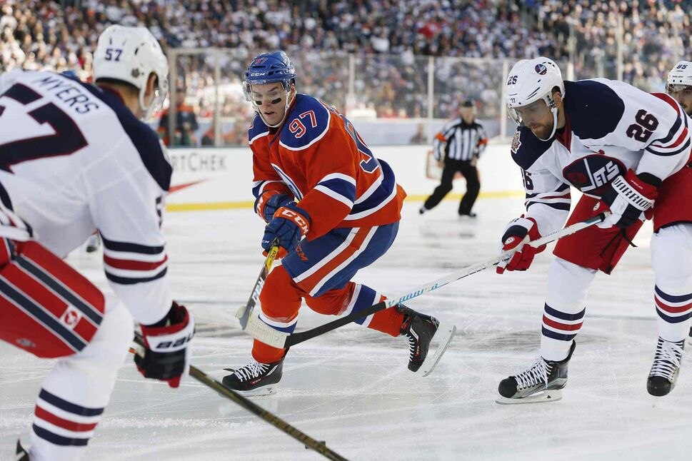 Edmonton Oilers' Connor McDavid (97) looks for the puck with Winnipeg Jets' Tyler Myers (57) and Blake Wheeler (26) during first period NHL Heritage Classic action in Winnipeg on Sunday, October 23, 2016.  (JOHN WOODS / The Canadian Press )