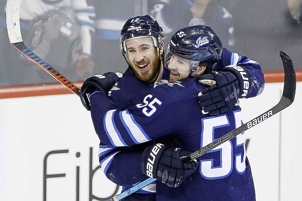 Kevin Hayes and Mark Scheifele celebrate Hayes' first goal for the Jets. (John Woods / The Canadian Press)