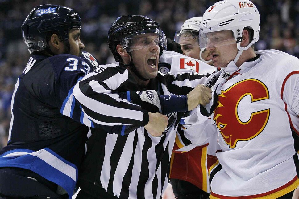 A linesman attempts to split up Winnipeg Jets' Dustin Byfuglien (33) and Calgary Flames' Ladislav Smid (3) and Chris Butler (44) after the second period buzzer goes during NHL action in Winnipeg on Monday, Nov. 18, 2013.  (John Woods / Winnipeg Free Press)