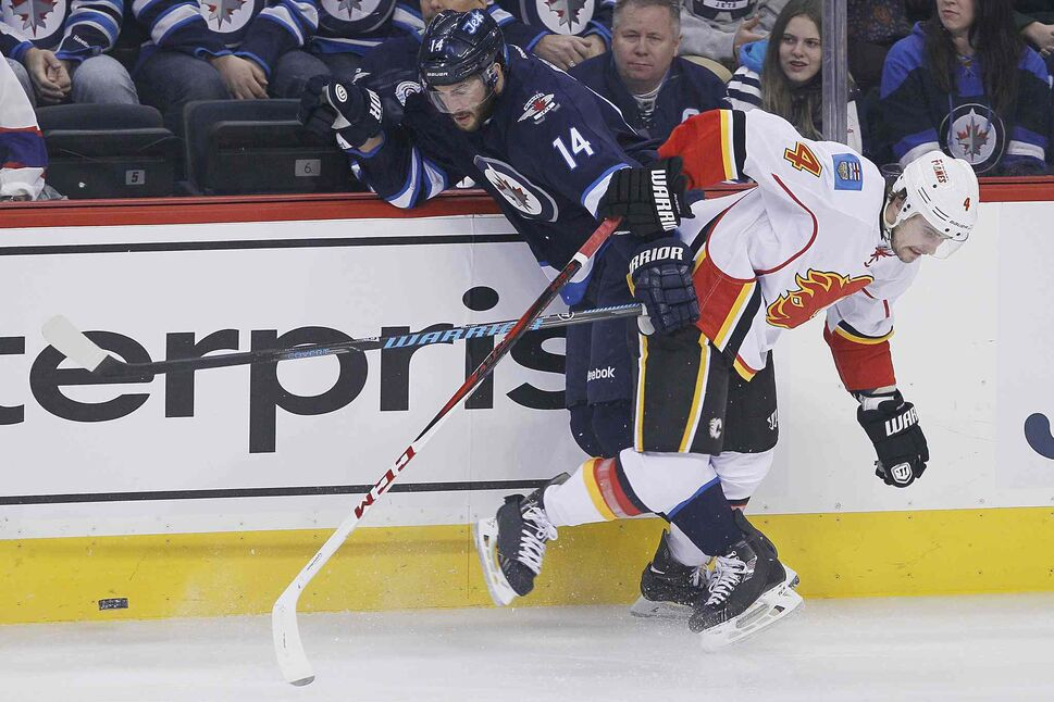 Winnipeg Jets' Anthony Peluso (14) and Calgary Flames' Kris Russell (4) collide during first period NHL action in Winnipeg on Monday, Nov. 18, 2013.  (John Woods / Winnipeg Free Press)