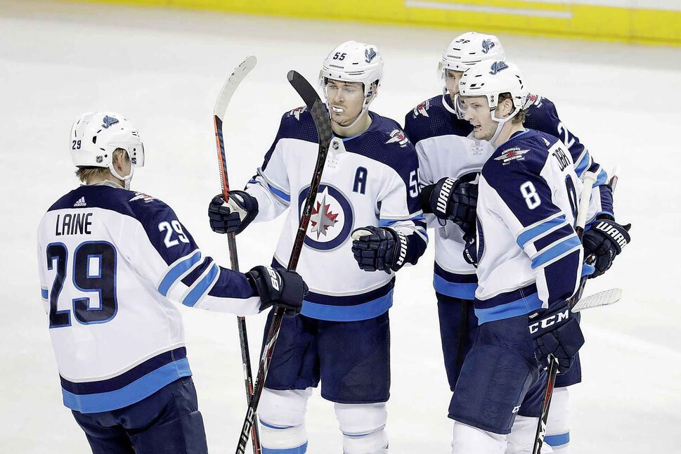 Winnipeg Jets players celebrate a goal by Jacob Trouba during the third period of their win over the New York Islanders, Tuesday.