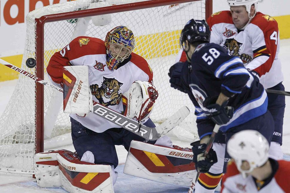 Winnipeg Jets' Eric O'Dell's (58) deflection is stopped by Florida Panthers goaltender Jacob Markstrom (25) as Panthers' Dylan Olsen (4) attempts to move O'Dell from in front of the net during the third period. (John Woods / The Canadian Press)