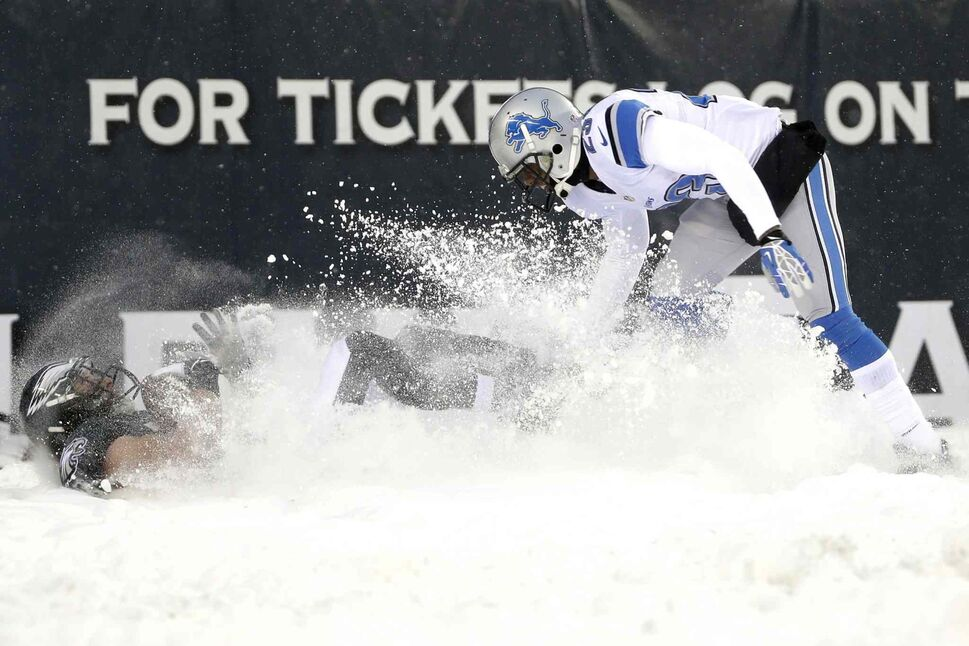 Philadelphia Eagles' Riley Cooper (left) kicks up the snow as he pulls in a two-point conversion as Chris Houston of the Detroit Lions defends during the second half. (Matt Rourke / The Associated Press)