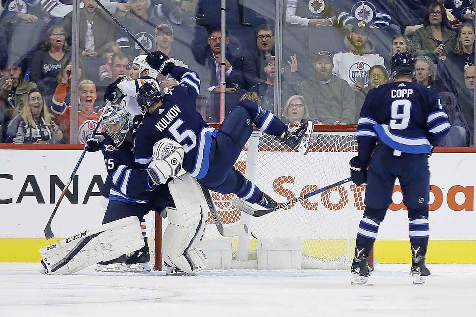 Winnipeg Jets' Dmitry Kulikov (5) crashes into his goaltender Steve Mason (35). (John Woods / THE CANADIAN PRESS)