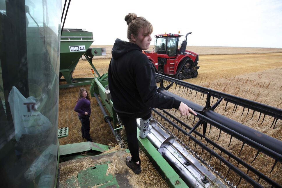 Kara (front, with Kaylie in background) checks the settings on the combine.</p></p>