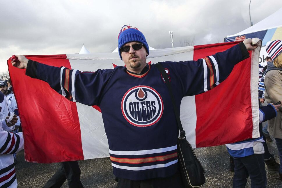 Andrew Lindsay wears a Canadian flag while among hundreds of fans gathered at the Spectator Plaza across the street from Inveastors Group Field on Sunday hours before the NHL game between the Winnipeg Jets and the Edmonton Oilers. (MIKE DEAL / WINNIPEG FREE PRESS)