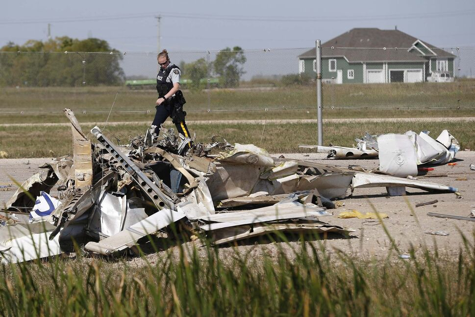 RCMP investigate at the scene of a fatal plane crash at St. Andrews Airport, north of Winnipeg, Thursday. (John Woods / The Canadian Press)